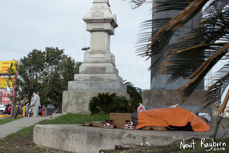 """A homeless person sleeps under The Battle of Liberty Place monument in New Orleans, Louisiana, January 2, 2016. Photograph © 2016 Newt Rayburn - newtrayburn@gmail.com. Cardboard sign reads """"NEED A BLESSING ANYTHING HELP"""""""